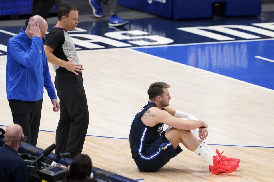 Dallas Mavericks head coach Rick Carlisle, left, places his hand to his head and guard Luka Doncic, right, sits on the court as referee Mark Lindsay, center, calls a foul against Doncic in the second half in Game 3 of an NBA basketball first-round playoff series against the Los Angeles Clippers in Dallas, Friday, May 28, 2021. (AP Photo/Tony Gutierrez)