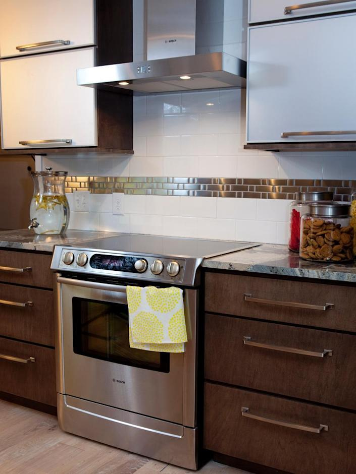 <p>A single, metallic stripe sets this kitchen backsplash apart while creating a streamlined look. Horizontal drawer pulls and a sleek range hood complete the modern design in this kitchen designed by HGTV's <i>Property Brothers</i>.</p>
