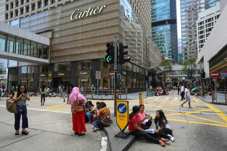 The city's army of domestic helpers sit in parks or on pavements, bridges and walkways on their one mandatory day off