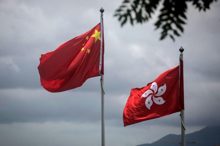 China's national flag is seen beside the Hong Kong ensign a day after protesters broke into the government headquarters in the city (AFP Photo/Vivek PRAKASH)