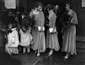 <p>Luxe fabrics of the era, such as velvet, were common for bridesmaids dresses. Here, the bridal party is seen in velvet long sleeve dresses, double stranded pearls, and a head wrap. </p>