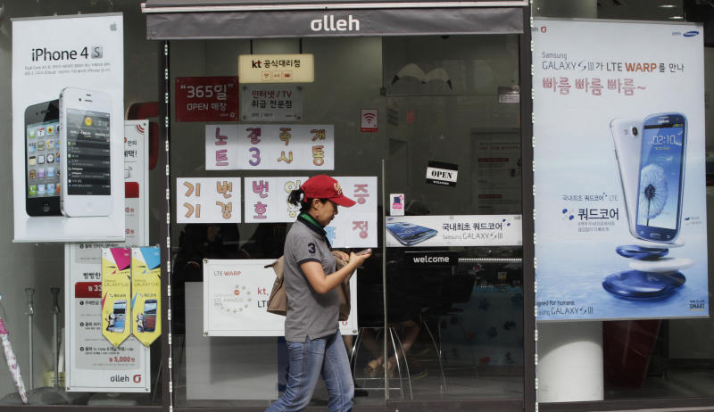 Advertising posters of Samsung Electronics' Galaxy S III, right, and Apple's iPhone 4S, left, are displayed at a mobile phone shop in Seoul, South Korea, Friday, Aug. 24, 2012. The Seoul Central District Court ruled Friday that technology rivals Apple Inc. and Samsung Electronics Co. both infringed on each other's patents, and ordered a partial ban of their products in South Korea. Each side was also ordered to pay limited damages.(AP Photo/Ahn Young-joon)