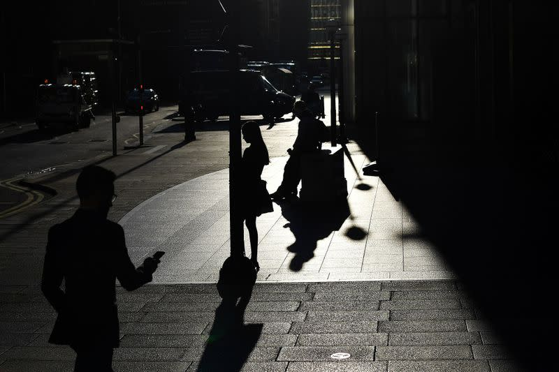 The early morning sun silhouettes commuters as they make their way through Canary Wharf in London
