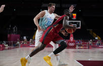 Germany's Isaac Bonga (0), right, drives to the basket past Slovenia's Luka Doncic (77) during men's basketball quarterfinal game at the 2020 Summer Olympics, Tuesday, Aug. 3, 2021, in Saitama, Japan. (AP Photo/Charlie Neibergall)