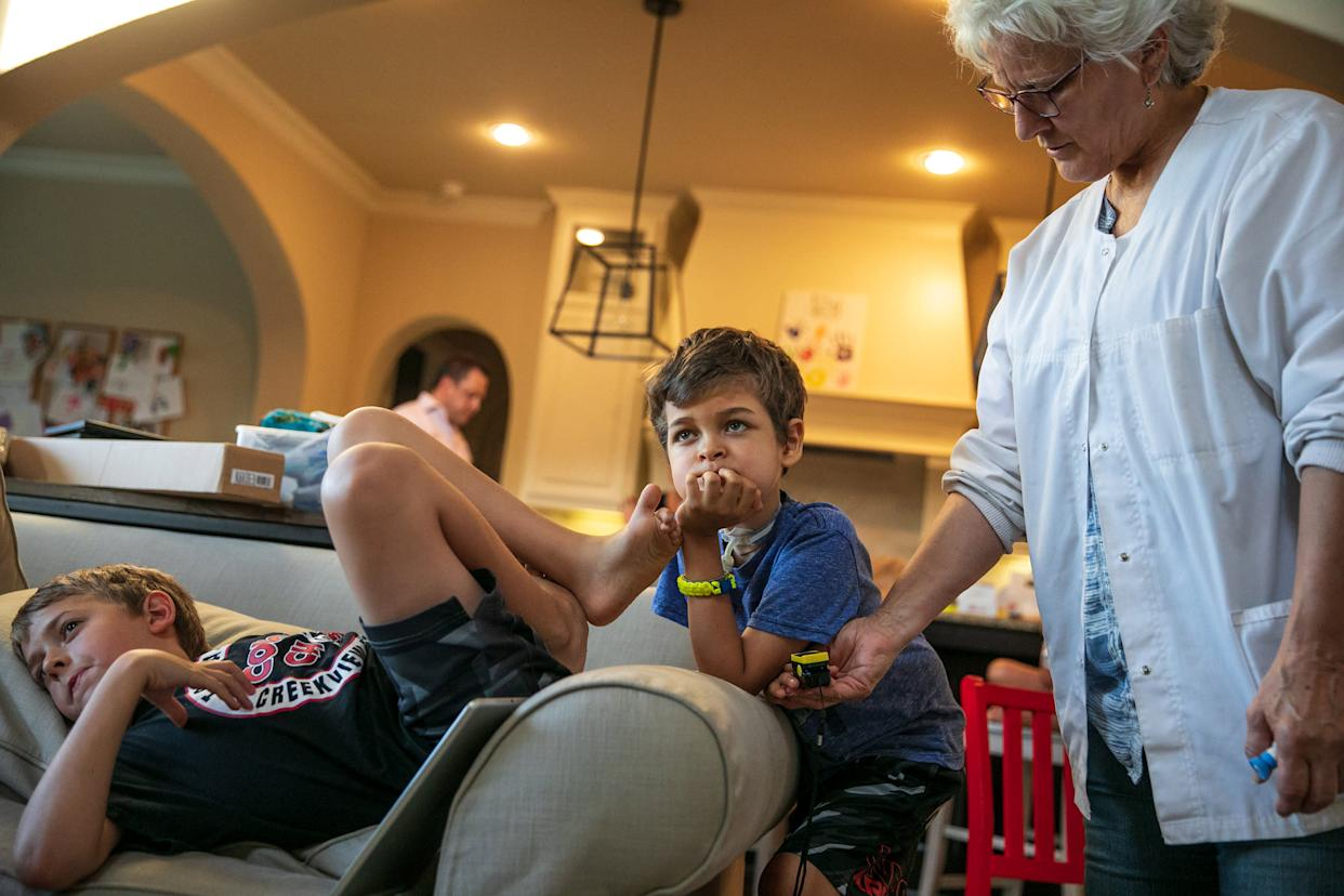 Caroline Casanova, LVN, one of Braden's nurses, checks his pulse and oxygen levels as he watches TV with his brother. | Ilana Panich-Linsman for TIME