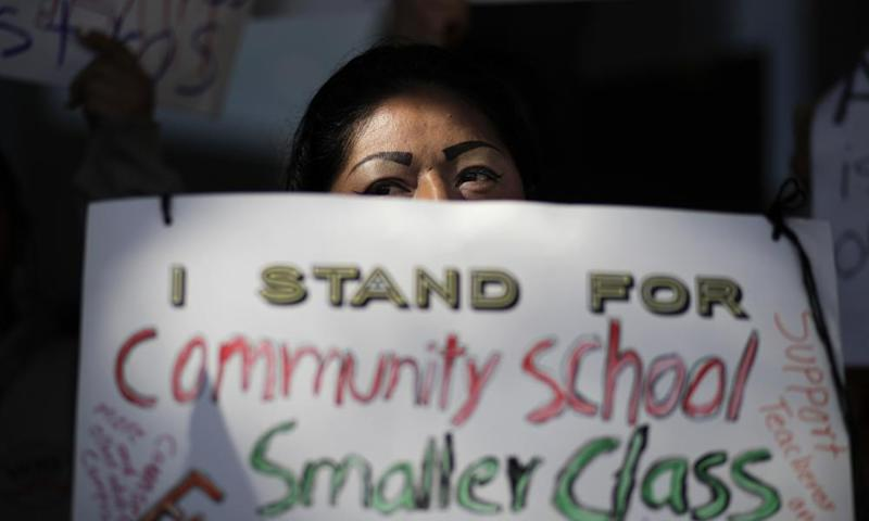 Manuela Panjoj, 42-year-old mother of five children, holds a sign during a news conference outside the Los Angeles Unified School District headquarters.