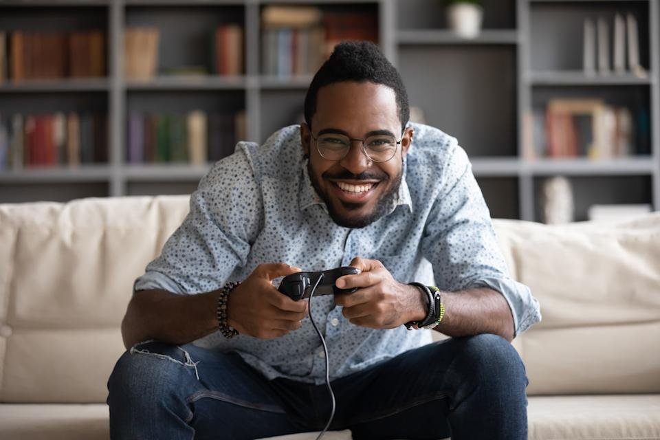 Overjoyed African American millennial man relax on couch in living room play video game using joystick gamepad, happy biracial young male gamer rest at home engaged in digital virtual activity