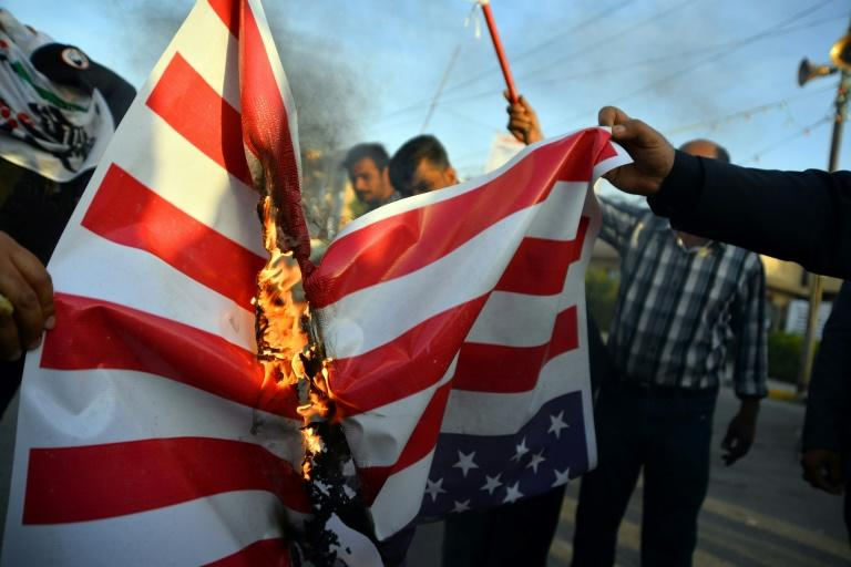 Iraqis torch an American flag after US air strikes against a pro-Iran group kill at least 25 fighters
