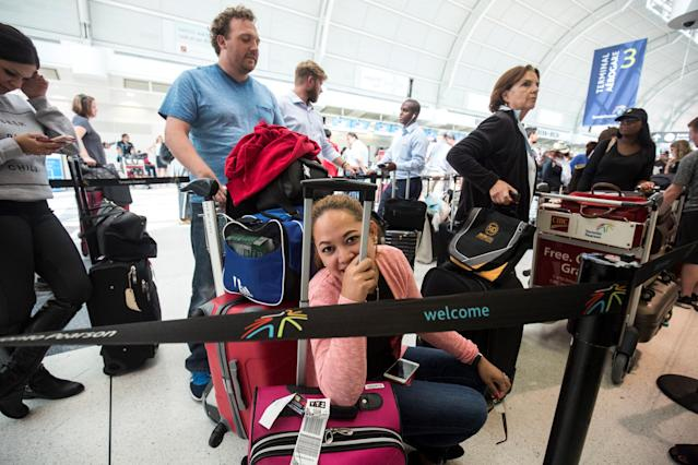 Milet McKeon, centre, uses her luggage as a seat as she waits in line at Pearson International airport, in Toronto, Canada on August 8, 2016. (Photo by Giordano Ciampini/Anadolu Agency/Getty Images)