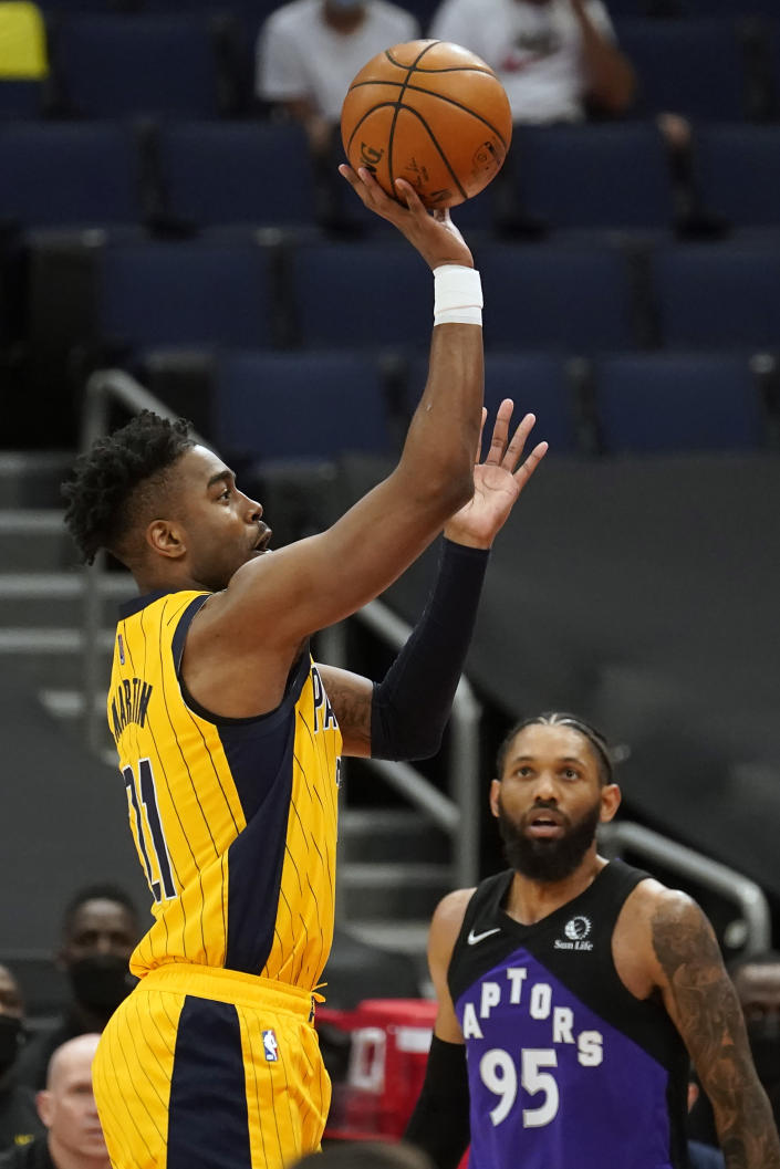 Indiana Pacers guard Kelan Martin (21) shoots over Toronto Raptors guard DeAndre' Bembry (95) during the first half of an NBA basketball game Sunday, May 16, 2021, in Tampa, Fla. (AP Photo/Chris O'Meara)
