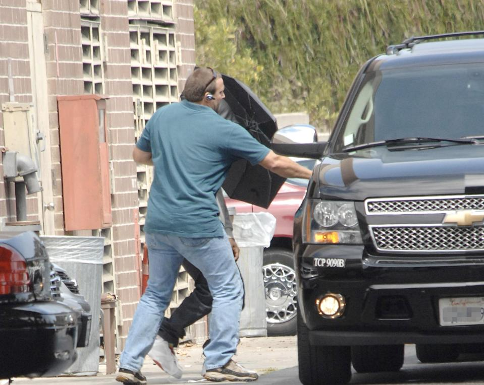 Kanye West does his best not to be photographed after being released from jail in Culver City, Calif., after he was charged with felony vandalism for smashing photographers' cameras at LAX in 2008. (Photo: Splash News)