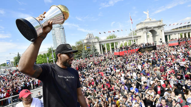 Toronto Raptors forward Kawhi Leonard holds his Finals MVP trophy as he celebrates during the championship parade. THE CANADIAN PRESS/Frank Gunn