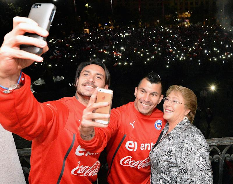 Chile President Michelle Bachelet (R) poses for a selfie with Chilean national football team players Gary Medel (C) and Mauricio Pinilla at La Moneda Presidential Palace in Santiago, in this June 29, 2014 handout photo