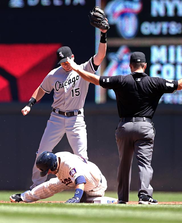 Second base umpire Mark Wegner signals Minnesota Twins' Brian Dozier safe at second but upon review, Dozier was called out and credited with a single in the third inning of a baseball game, Saturday, June 21, 2014, in Minneapolis. Making the tag is Chicago White Sox second baseman Gordon Beckham (AP Photo/Jim Mone)