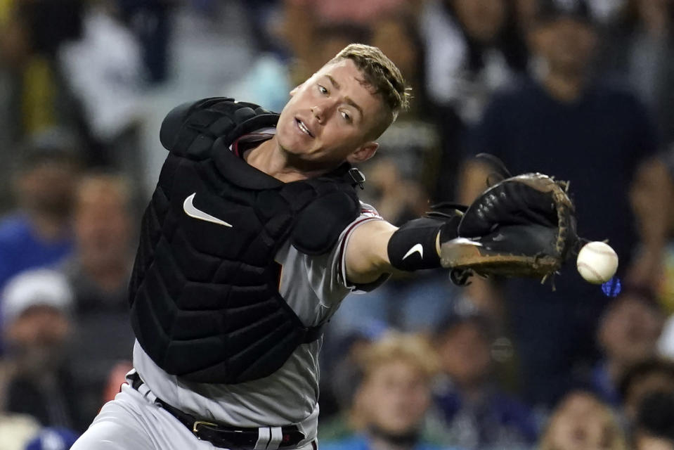 Arizona Diamondbacks catcher Carson Kelly reaches but cannot catch a foul ball from Los Angeles Dodgers' Cody Bellinger during the seventh inning of a baseball game Monday, Sept. 13, 2021, in Los Angeles. (AP Photo/Marcio Jose Sanchez)