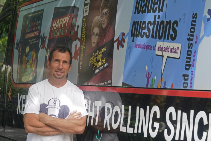"""Toy maker Eric Poses stands at his home, Wednesday, Aug. 4, 2021, in Miami Beach, Fla. Poses created a card game last year called """"The Worst-Case Scenario"""", a wry reference to the way the coronavirus had upended normal life. Poses' game was caught in the global supply chain that has delayed shipments around the world and sent freight costs rocketing. Poses is the owner of the toy company, All Things Equal. (AP Photo/Marta Lavandier)"""