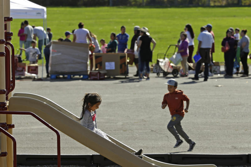 Children play on the playground while people line up for a free food distribution for migrant workers evacuated because of the Kincade Fire Thursday, Oct. 31, 2019, in Healdsburg, Calif. (AP Photo/Charlie Riedel)