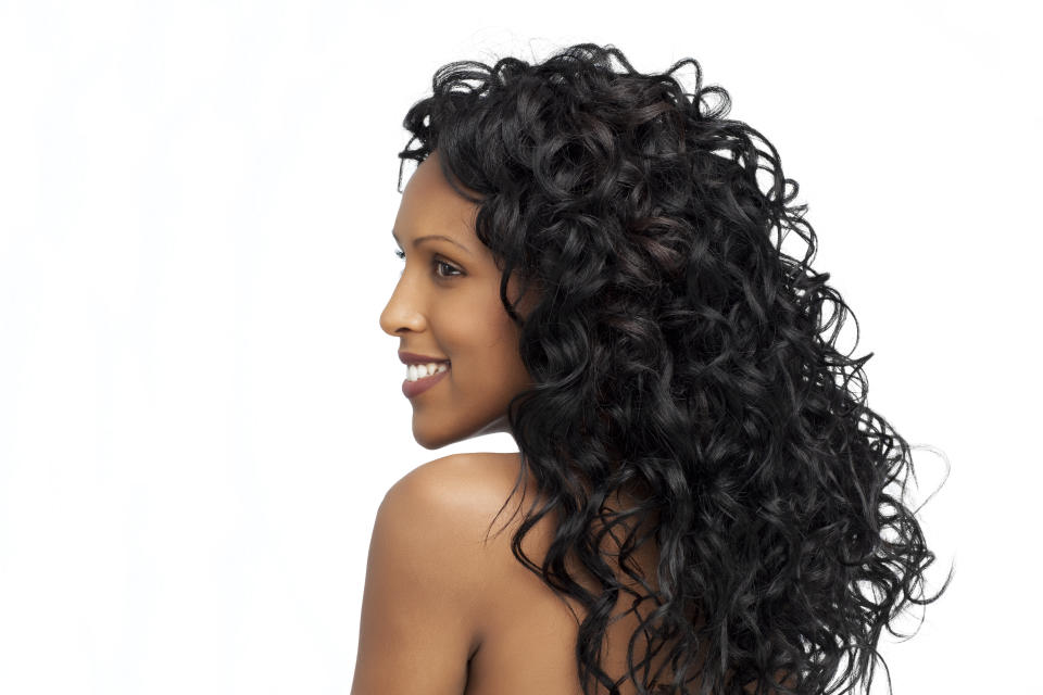 Profile of beautiful smiling woman with long curly hair, side view.