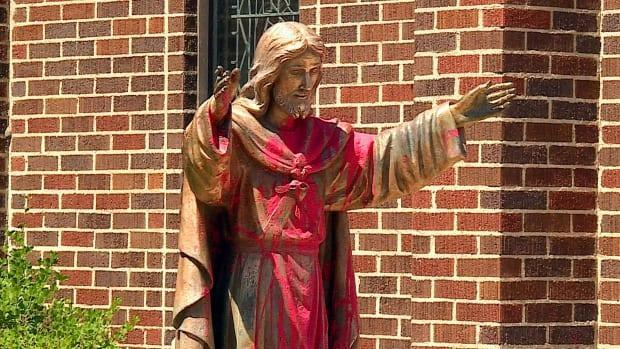 A statue of Jesus was covered with red paint outside of Sacred Heart Catholic Church in Sunalta in southwest Calgary. A man has been charged in connection with two of the church vandalisms which occurred this summer.  (Julie Debeljak/CBC - image credit)