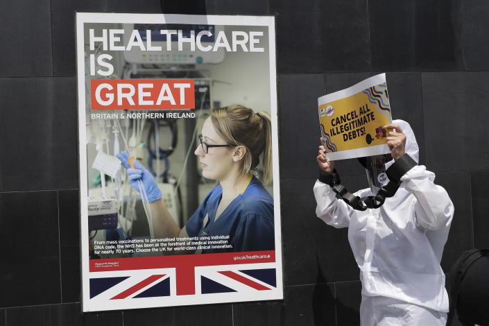 A protester dressed in a protective suit holds slogans during a rally against the G7 summit outside the British Embassy in Taguig, Philippines on Friday, June 11, 2021. The group called on G7 Summit member nations for debt cancellation for poor countries facing difficulties due to the COVID-19 pandemic. (AP Photo/Aaron Favila)