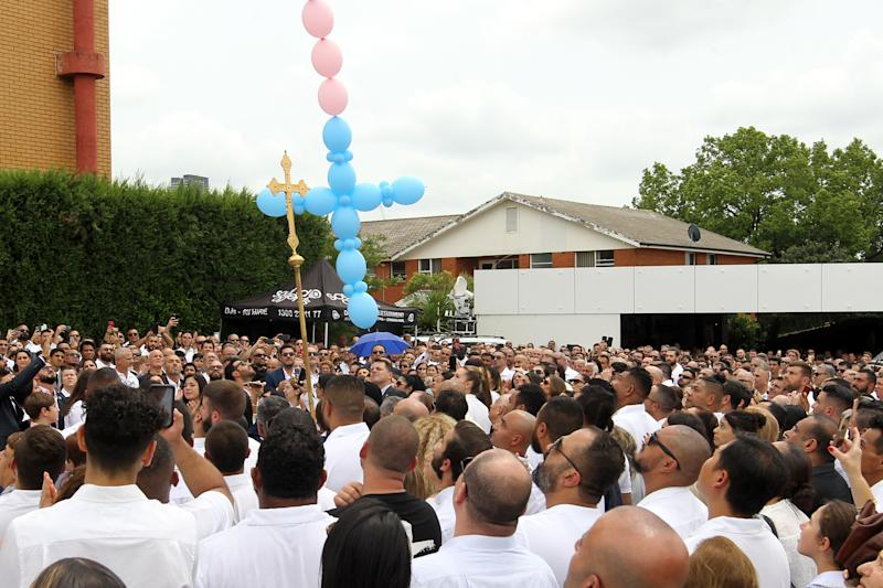 Mourners watch on a tribute is relesed to Antony, 13, Angelina, 12 and eight-year-old Sienna Abdallah during their funeral at Our Lady of Lebanon Co-Cathedral, Monday, February 10, 2020. The three siblings run down and killed by an alleged drunk driver in Oatlands, in Sydney's west. (AAP Image/Danny Casey) NO ARCHIVING