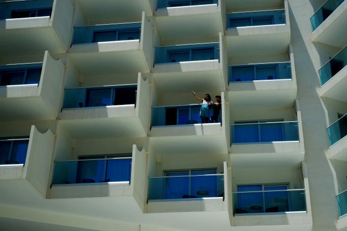 A woman and a boy stand at a balcony of a room of Nissi Blue hotel in southeast resort of Ayia Napa, in the eastern Mediterranean island of Cyprus, Saturday, May 22, 2021. Cypriot hotel and other tourism-related business owners say they'd like to see the COVID-19 pandemic-induced uncertainty over travel bookings to the tourism-reliant island nation winding down by July when they're hoping authorities in Cyprus' main markets including the U.K., Russia, Germany and the Scandinavian countries will make it easier for their citizens to travel abroad. (AP Photo/Petros Karadjias)