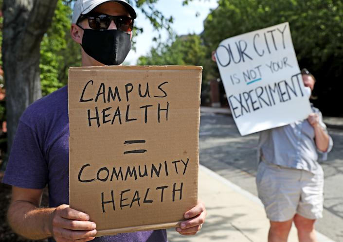 "Protesters hold signs reading ""Campus health = community health"" and ""Our city is not your experiment."""