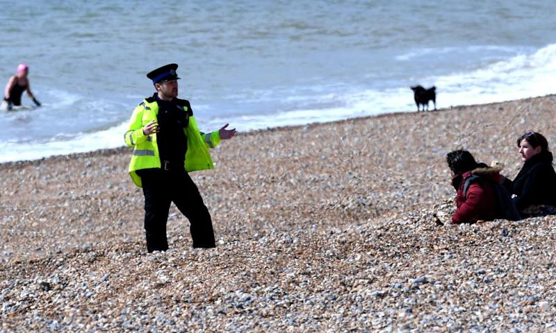 A police officer asks people to leave the beach at Brighton.