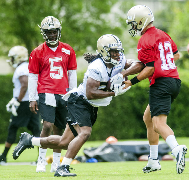 New Orleans Saints quarterback J.T. Barrett (5) stands by as running back Trey Edmunds is handed the ball by quarterback Tom Savage (12) during NFL football practice in Metairie, La., Thursday, May 24, 2018. (AP Photo/Sophia Germer)