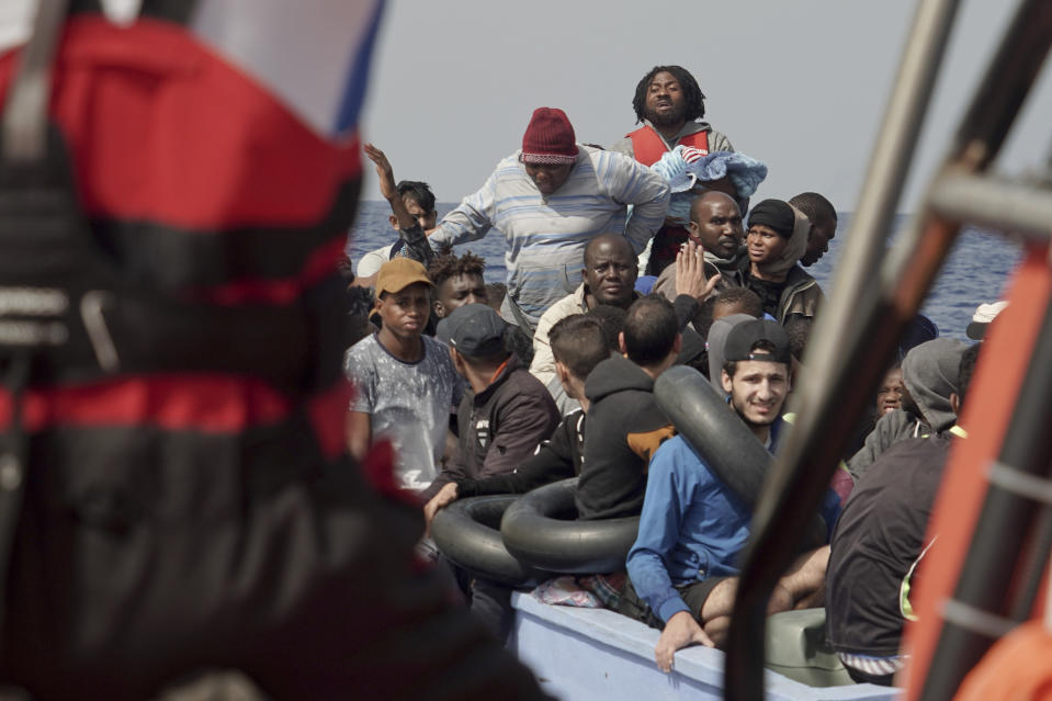 Migrants react to SOS Mediterranee's team during a rescue operation some 53 nautical miles (98 kilometers) from the coast of Libya in the Mediterranean Sea, Tuesday, Sept. 17, 2019. The humanitarian rescue ship Ocean Viking pulled 48 people from a small and overcrowded wooden boat including a newborn and a pregnant woman. (AP Photo/Renata Brito)