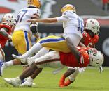 Miami defensive tackle Nesta Jade Silvera (1) tackles Pittsburgh quarterback Joey Yellen (16) in the second quarter of an NCAA college football game at Hard Rock Stadium in Miami Gardens, Fla., Saturday, Oct. 17, 2020. (Al Diaz/Miami Herald via AP)