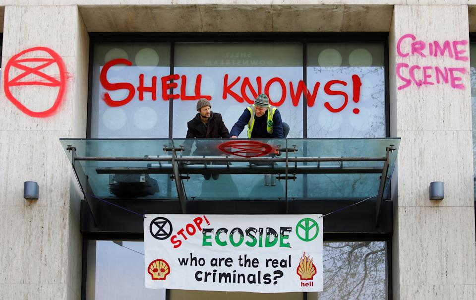A climate activist sprays graffiti on the entrance to the Shell's British offices. (Photo: TOLGA AKMEN via Getty Images)