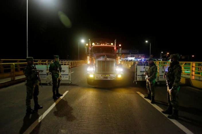 Soldiers keep watch near a trailer truck carrying food at Rumichaca International Bridge between Colombia and Ecuador, after Ecuador's government closed its borders to all foreign travelers due to the spread of the coronavirus disease, in Tulcan
