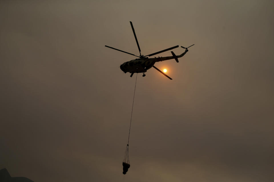 A firefighting helicopter takes water from the Aegean Sea near the Kemerkoy Power Plant, a coal-fueled power plant, in Milas, Mugla in southwest Turkey, Thursday, Aug. 5, 2021. A wildfire that reached the compound of a coal-fueled power plant in southwest Turkey and forced evacuations by boats and cars, was contained on Thursday after raging for some 11 hours, officials and media reports said. (AP Photo/Emre Tazegul)