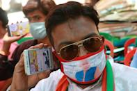 A supporter of Bharatiya Janata Party (BJP) wearing a Indian Prime Minister Narendra Modi photo and BJP Party logo printed mask watches India's Home Minister Amit Shah speaking during an online rally on a mobile phone screen in Kolkata on June 09,2020 ,India. (Photo by Debajyoti Chakraborty/NurPhoto via Getty Images)