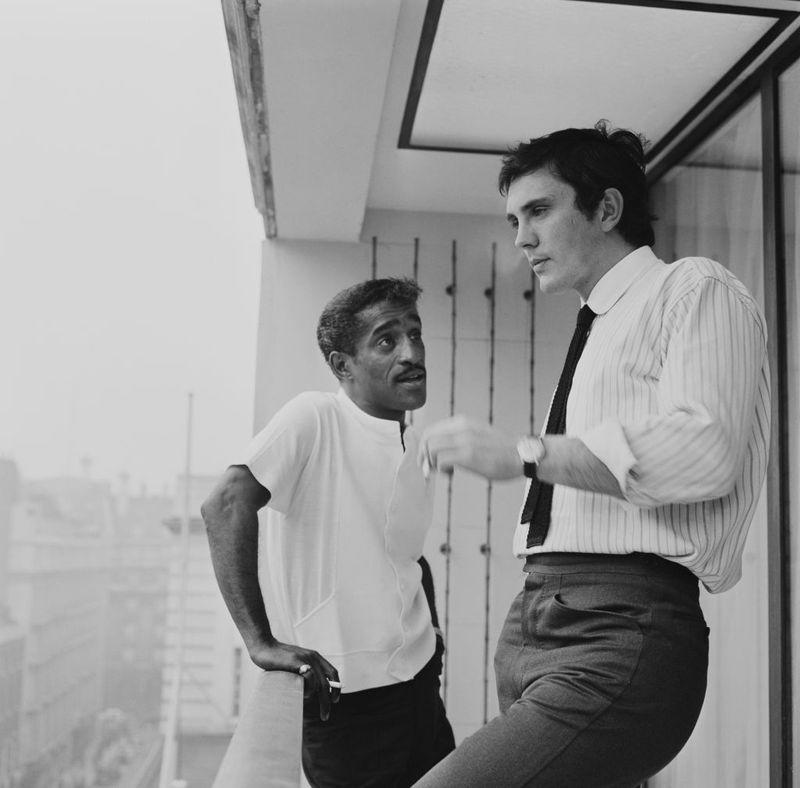 <p>Sammy Davis Jr. chats with actor Terence Stamp, while taking a cigarette break on the balcony of his London hotel room in 1963.</p>