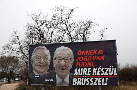 "FILE PHOTO: A government billboard is seen in Budapest, Hungary, March 13, 2019. The billoard reads, ""You also have the right to know what Brussels is up to"", accusing European Commission President Jean-Claude Juncker of pushing migration plans encouraged by U.S.-Hungarian businessman George Soros, in a media campaign rebuked by the commission. REUTERS/Bernadett Szabo - RC124BA15810/File Photo"