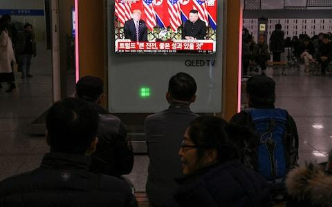 A television screen shows a news broadcast of North Korea's leader Kim Jong Un meeting with US President Donald Trump in Hanoi, at a railway station in Seoul - Credit: JUNG YEON-JE/AFP/Getty Images