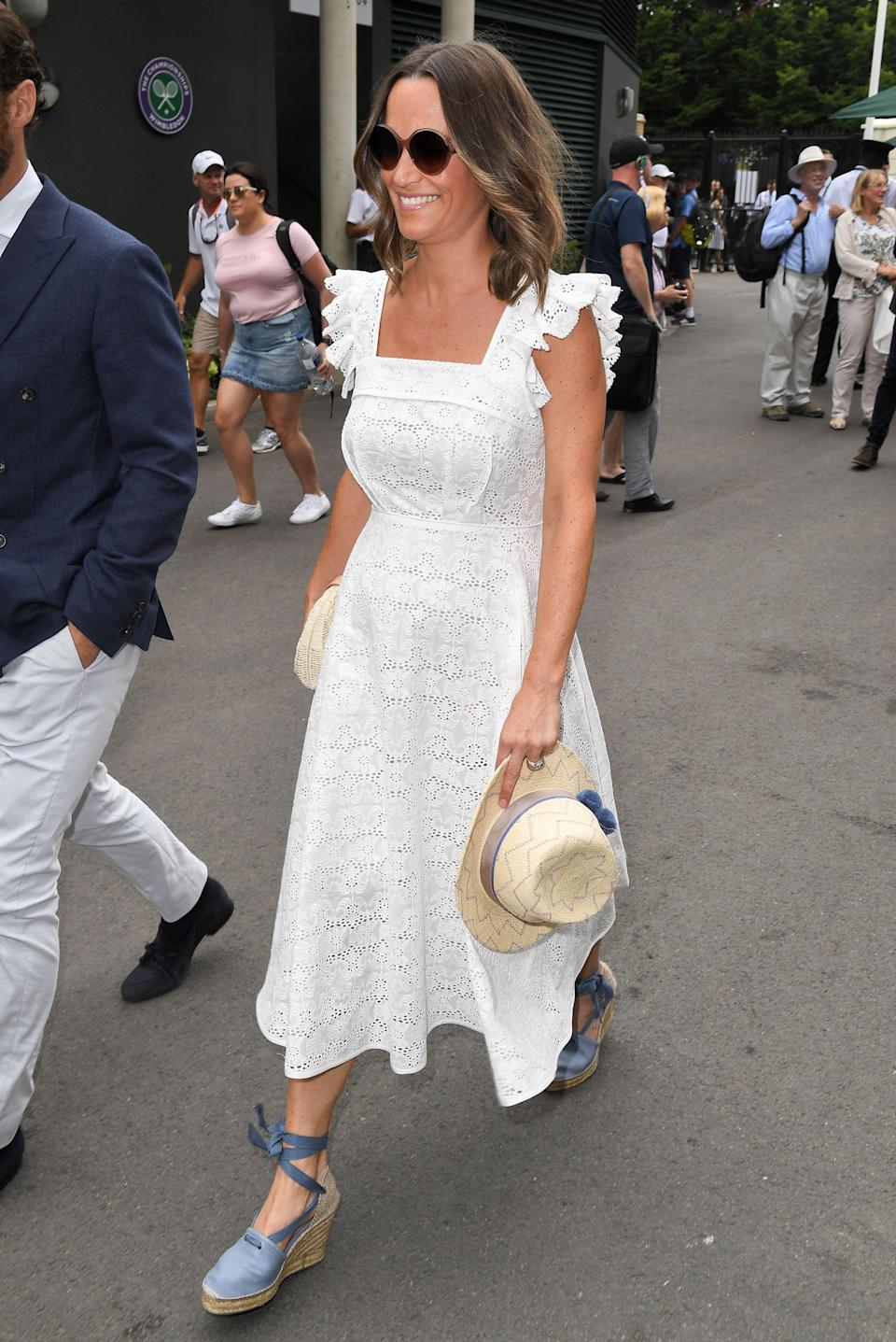 <p>Pippa Middleton arrived at Wimbledon 2018 with her brother James on 5 July. For the prestigious tournament, she donned a £680 broderie anglaise dress with frilled cap sleeves by Anna Mason London. To accessorise the look, she chose a £229.00 hat and clutch by Jess Collett. <em>[Photo: Rex]</em> </p>