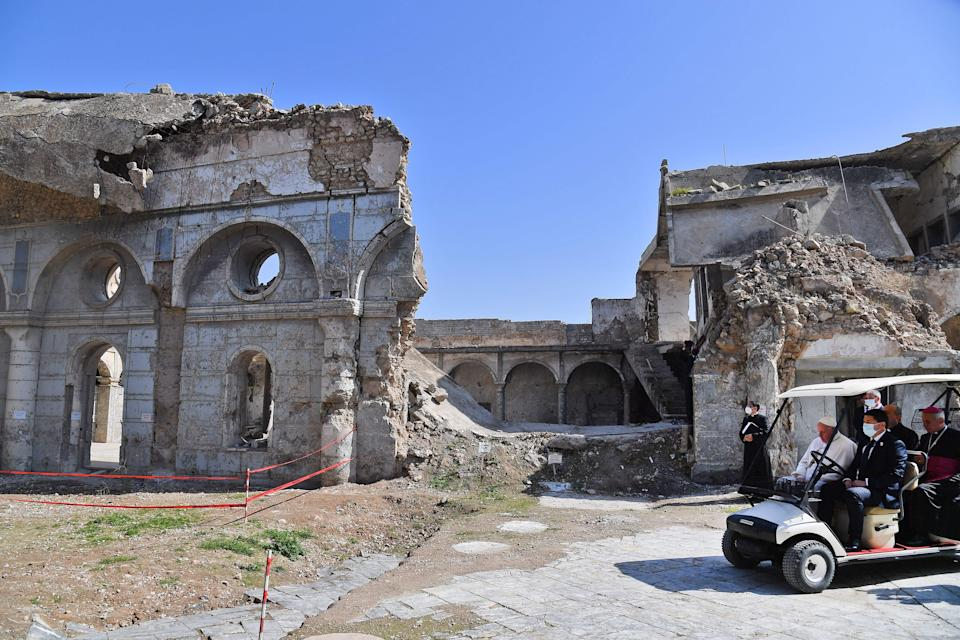 Pope Francis rides in a golf cart at the ruins of the Syriac Catholic Church of the Immaculate ConceptionAFP/Getty