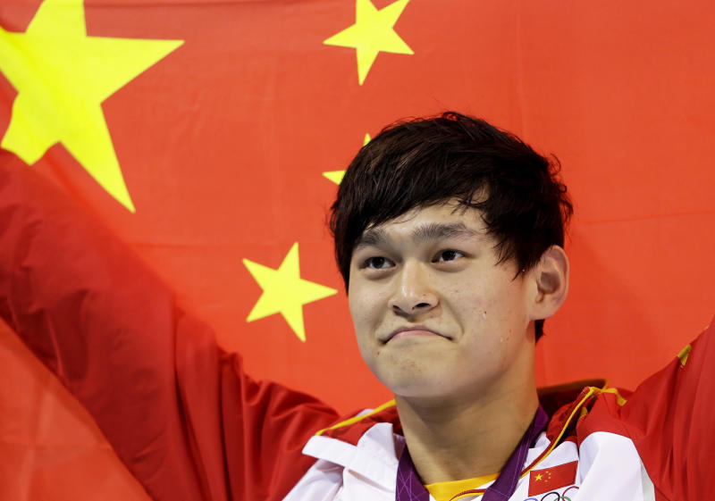 FILE - In this Saturday, Aug. 4, 2012 file photo, China's Sun Yang holds his national flag after winning the gold medal in the men's 1500-meter freestyle swimming final at the Aquatics Centre in the Olympic Park during the 2012 Summer Olympics in London. Chinese swimmer Sun Yang has been banned for eight years for breaking anti-doping rules and will miss the 2020 Tokyo Olympics. (AP Photo/Lee Jin-man, File)