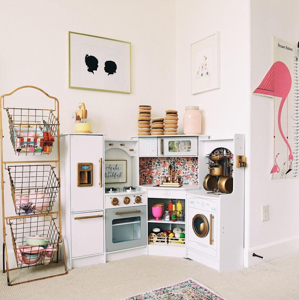 """<p>Set up a full-fledged toy kitchen corner and have your child store their pots and pans just like you do in your kitchen.</p><p><strong>See more at </strong><strong><a href=""""http://www.hellobabybrown.com/2017/01/playroom-tour.html"""" rel=""""nofollow noopener"""" target=""""_blank"""" data-ylk=""""slk:Hello, Baby Brown"""" class=""""link rapid-noclick-resp""""> Hello, Baby Brown</a>.</strong></p><p><strong><a class=""""link rapid-noclick-resp"""" href=""""https://www.amazon.com/s?k=wire+baskets&ref=nb_sb_noss_2&tag=syn-yahoo-20&ascsubtag=%5Bartid%7C10063.g.36014277%5Bsrc%7Cyahoo-us"""" rel=""""nofollow noopener"""" target=""""_blank"""" data-ylk=""""slk:SHOP WIRE BASKETS"""">SHOP WIRE BASKETS</a><br></strong></p>"""