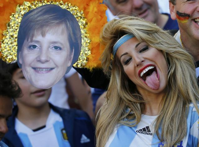 An Argentina fan reacts near a mask of German Chancellor Angela Merkel before the team's 2014 World Cup final against Germany at the Maracana stadium in Rio de Janeiro July 13, 2014. REUTERS/Kai Pfaffenbach (BRAZIL - Tags: SOCCER SPORT WORLD CUP)