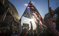 FILE - This photo from Sunday May 31, 2020, shows a man holds a U.S. flag upside down—a sign of distress, as protesters march in Brooklyn, N.Y., during a rally for George Floyd, a black man who died in Minneapolis after being restrained by police officers. (AP Photo/Wong Maye-E, File)