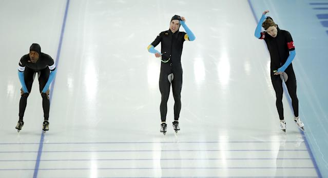 The U.S. speedskating team, left to right, Shani Davis, Jonathan Kuck and Brian Hansen catch their breath after competing in the men's speedskating team pursuit quarterfinals at the Adler Arena Skating Center during the 2014 Winter Olympics in Sochi, Russia, Friday, Feb. 21, 2014. (AP Photo/Pavel Golovkin)