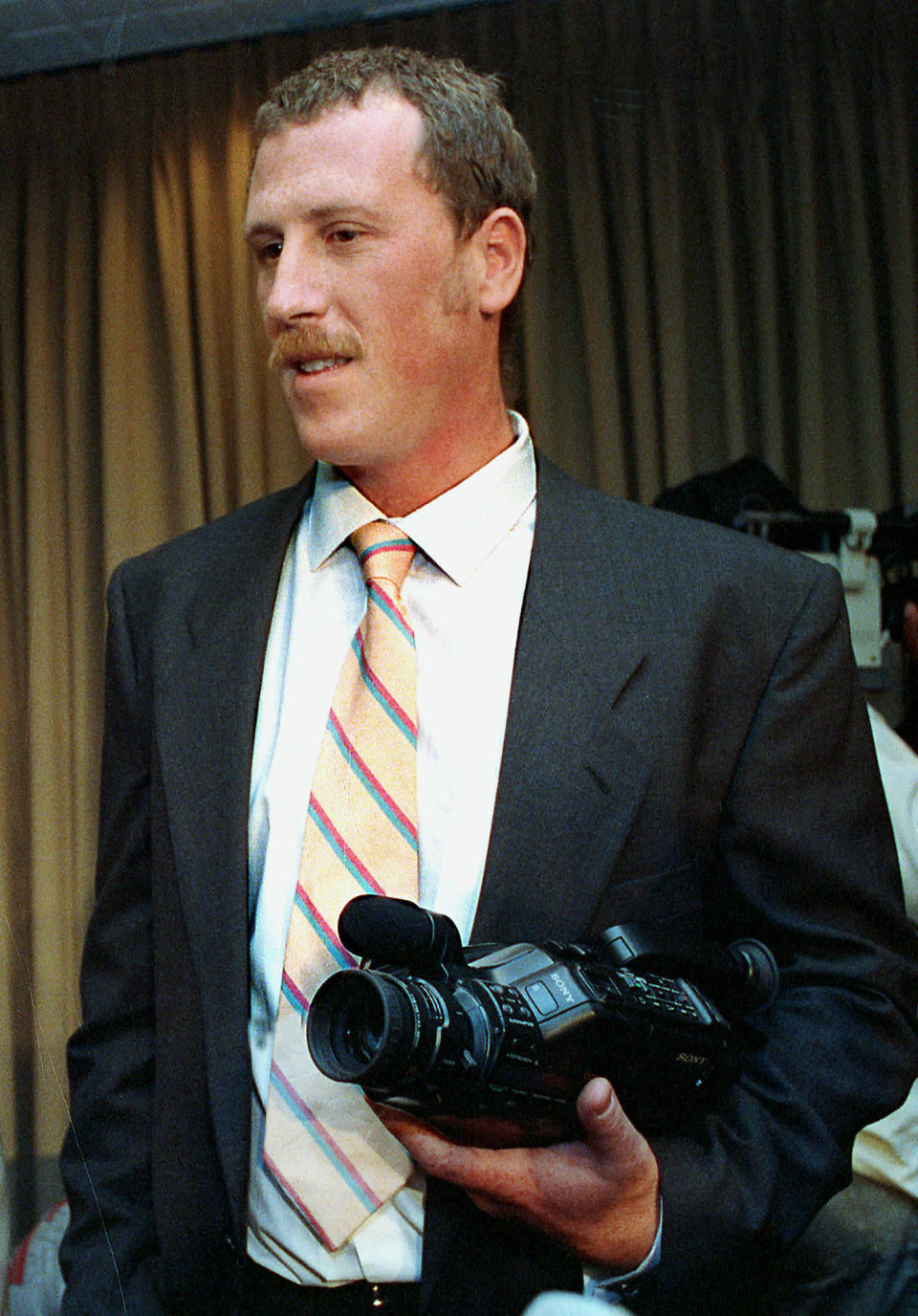 FILE - In this March 28, 1991, file photo, George Holliday, the man who videotaped the beating of Black motorist Rodney King by four Los Angeles Police Department officers, holds his camera after a news conference, in Los Angeles. Holliday has died from COVID-19, it was reported Monday, Sept. 20, 2021. (AP Photo/Craig Fujii, File)