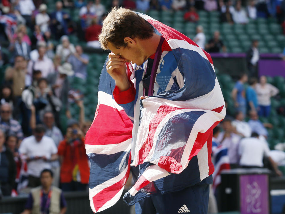 Britain's Andy Murray drapes himself with the flag during the presentation ceremony after winning the men's singles tennis gold medal match against Switzerland's Roger Federer at the All England Lawn Tennis Club during the London 2012 Olympic Games August 5, 2012. REUTERS/Stefan Wermuth (BRITAIN - Tags: OLYMPICS SPORT TENNIS)