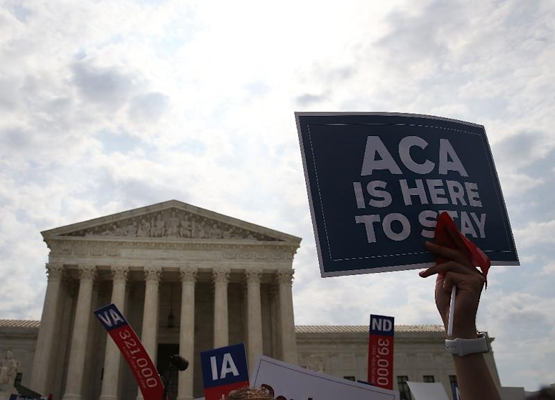 """A sign is held up that reads """"ACA Is Here To Stay"""" in front of the US Supreme Court after a ruling was announced in favor of the Affordable Care Act on June 25, 2015 in Washington, DC"""