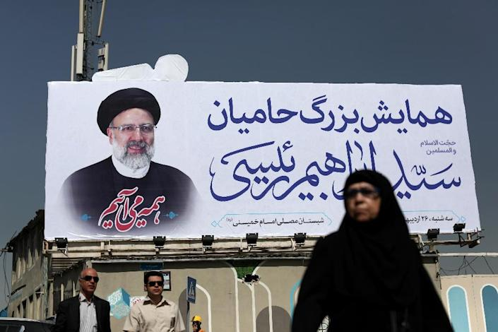 An Iranian woman walks past a portrait of presidential candidate Ebrahim Raisi in Tehran on May 15, 2017 (AFP Photo/Behrouz MEHRI)