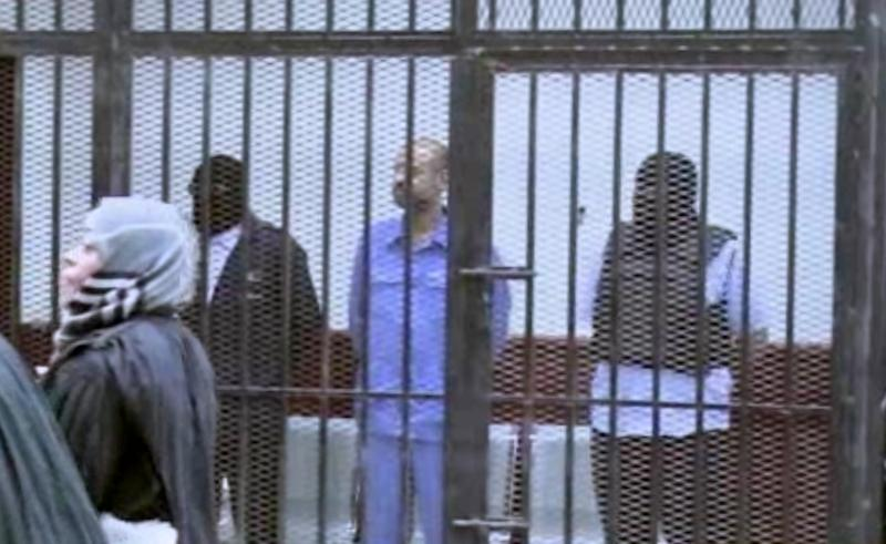This image made from AP video shows Seif al-Islam Gadhafi, son of Libya's former dictator Moammar Gadhafi, inside a cage in a courtroom in Zintan, Libya, Thursday, Sept. 19, 2013. A militia-run prison failed to transfer Gadhafi to a pre-trial hearing in Tripoli on Thursday, underscoring the central government's difficulty in asserting its authority since the end of the country's civil war.(AP Photo via AP video)